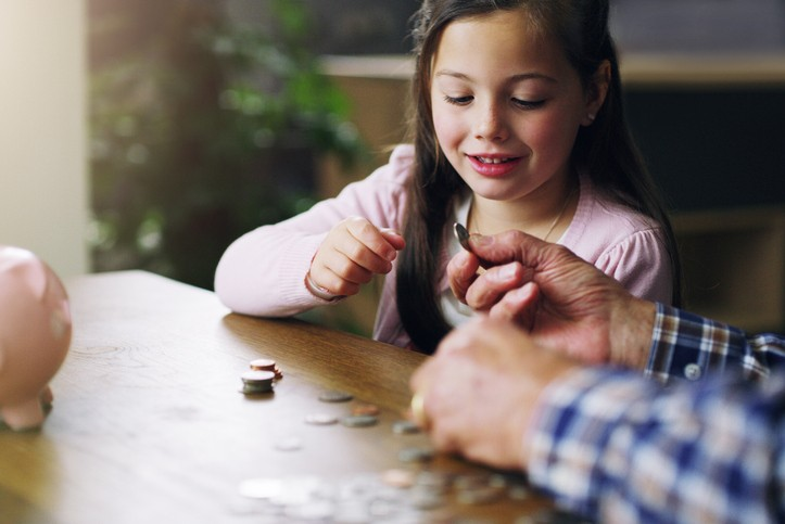 A young girl practicing counting coins to enforce math skills.