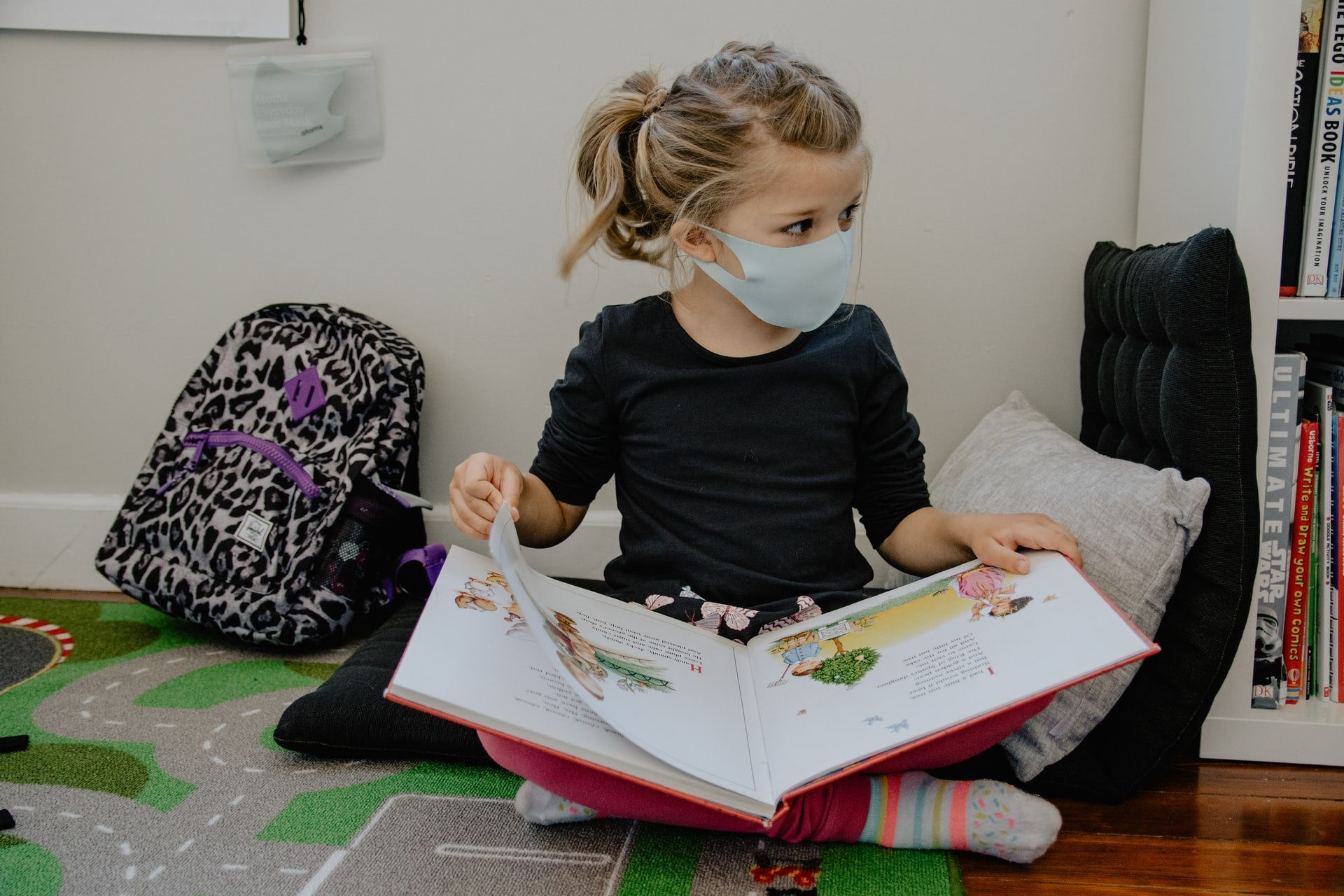 A young girl wearing a mask reads a book in a classroom.