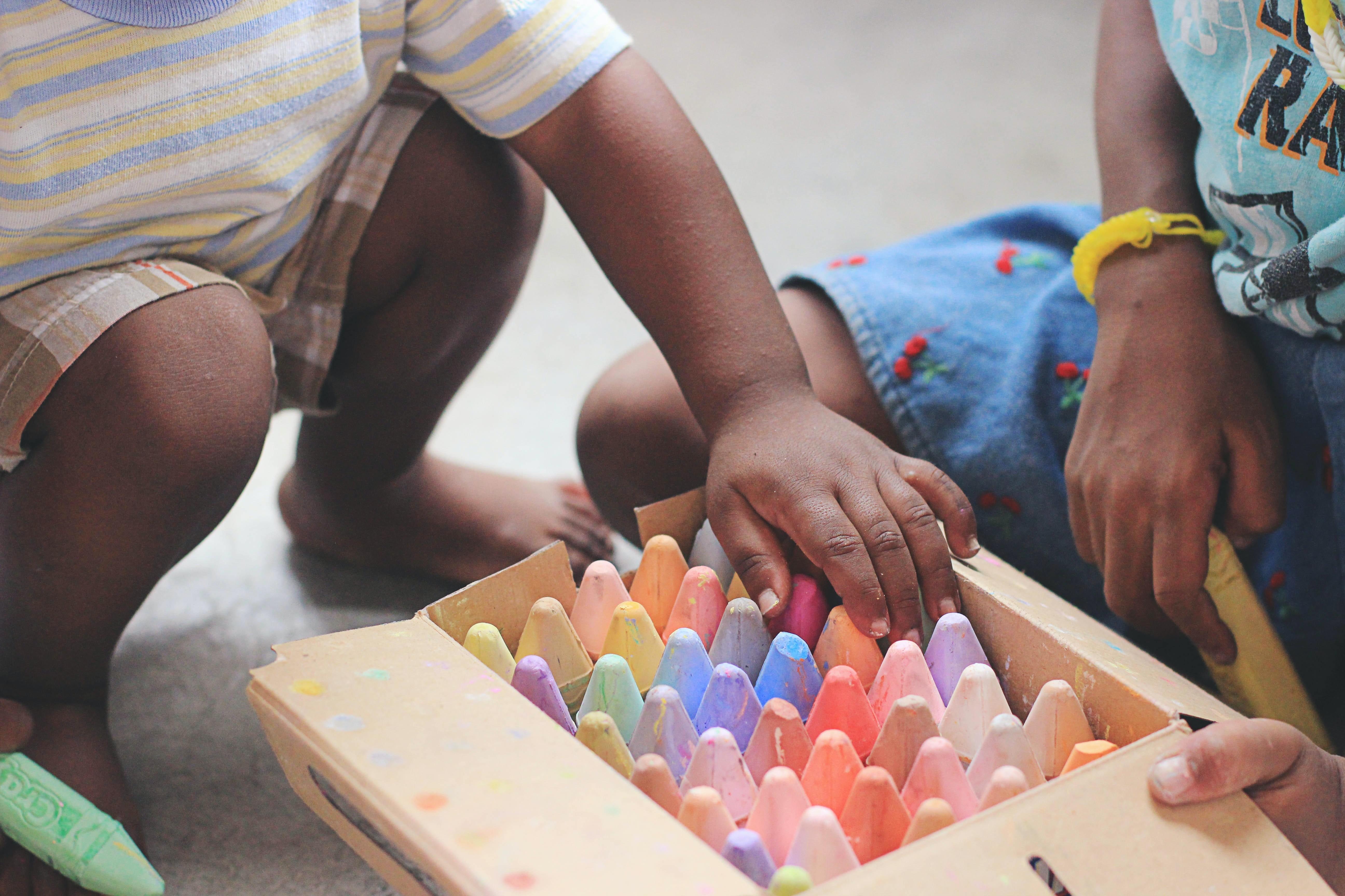 Two children sharing sidewalk chalk.