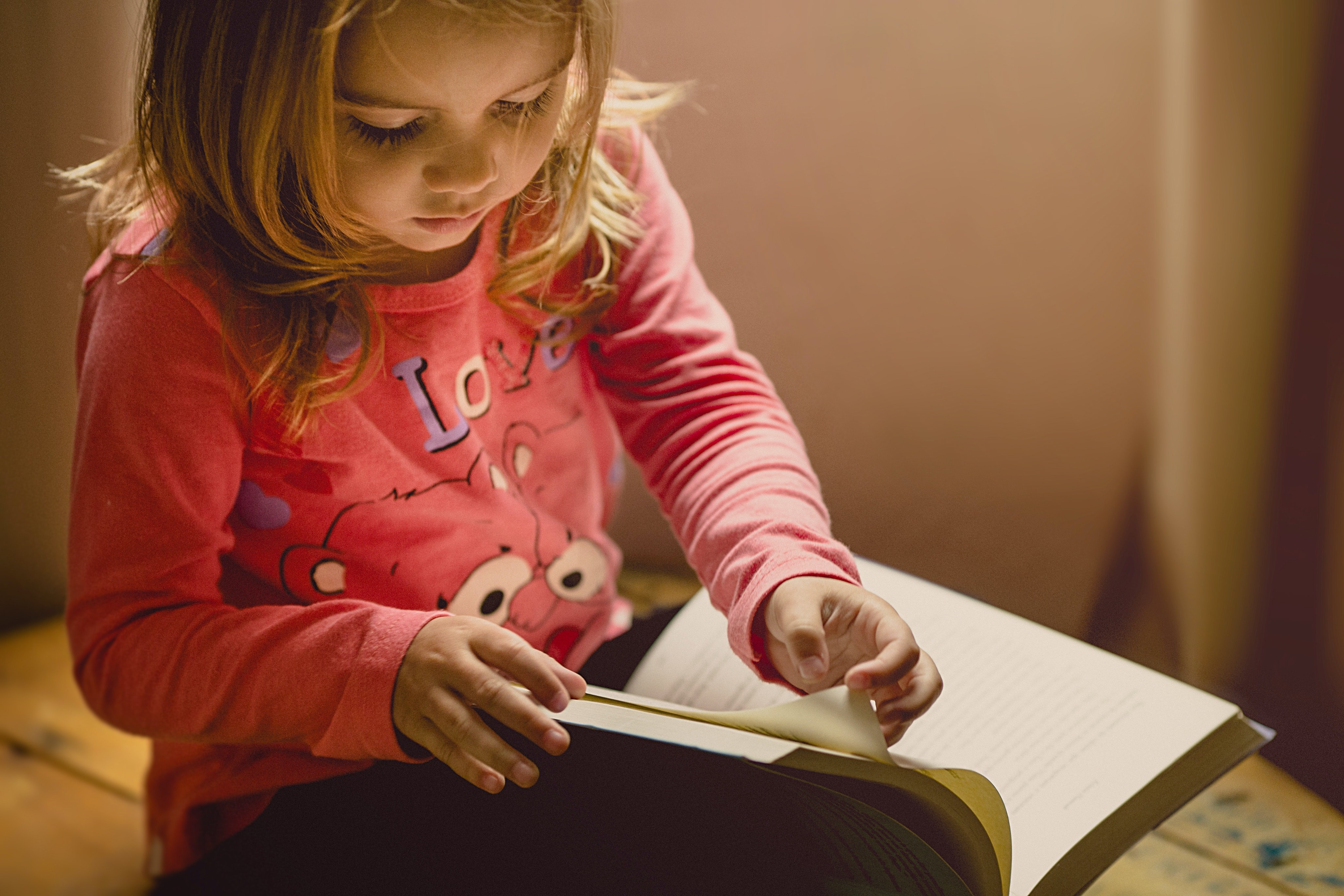 A young girl practicing first grade reading skills.