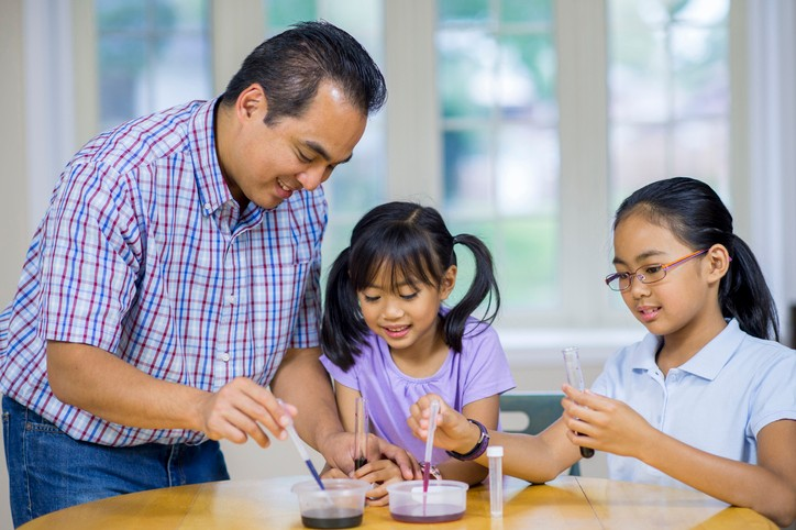 A father helps his two young daughters with an at-home science experiment.