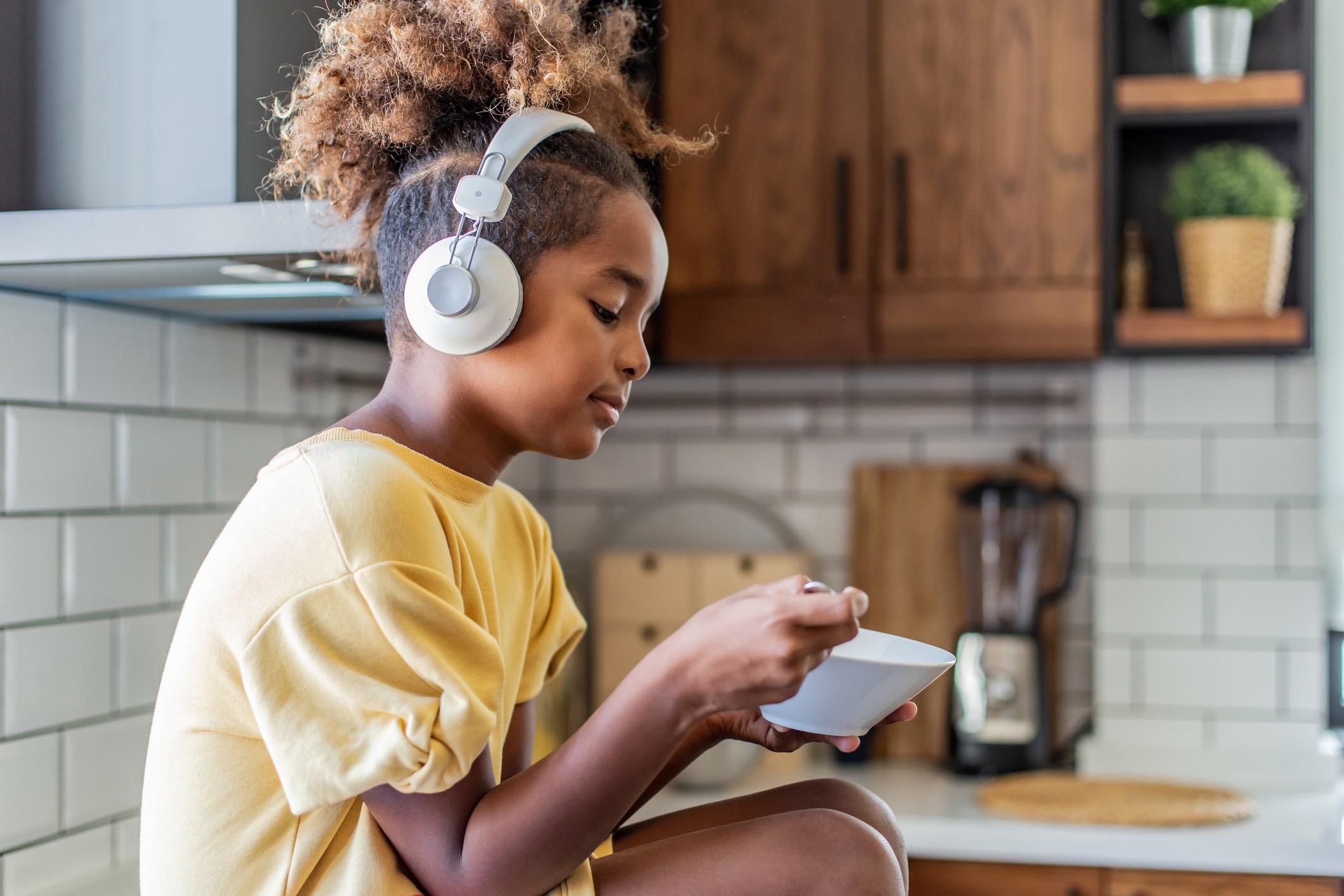 Young girl wearing headphones in her kitchen.