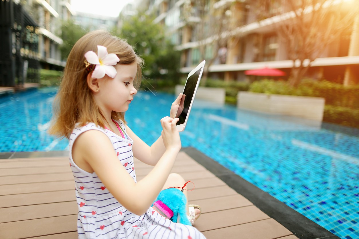 Child sitting by a pool on a tablet device.
