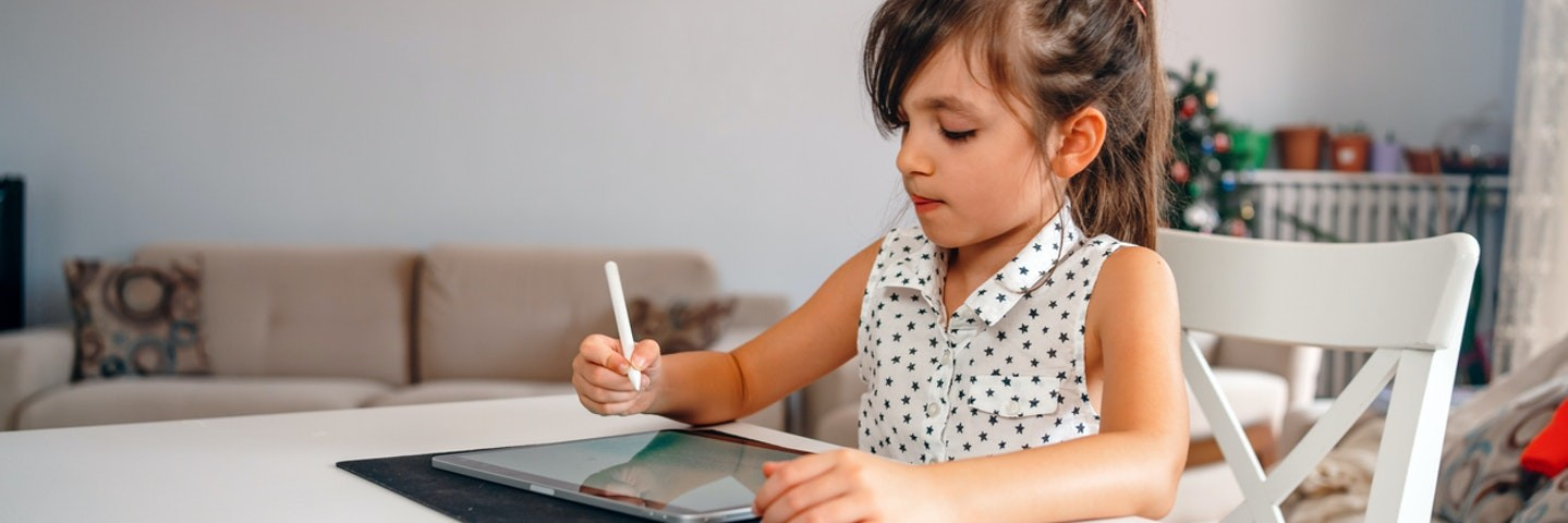 A young girl sitting at a table preparing for first grade learning.