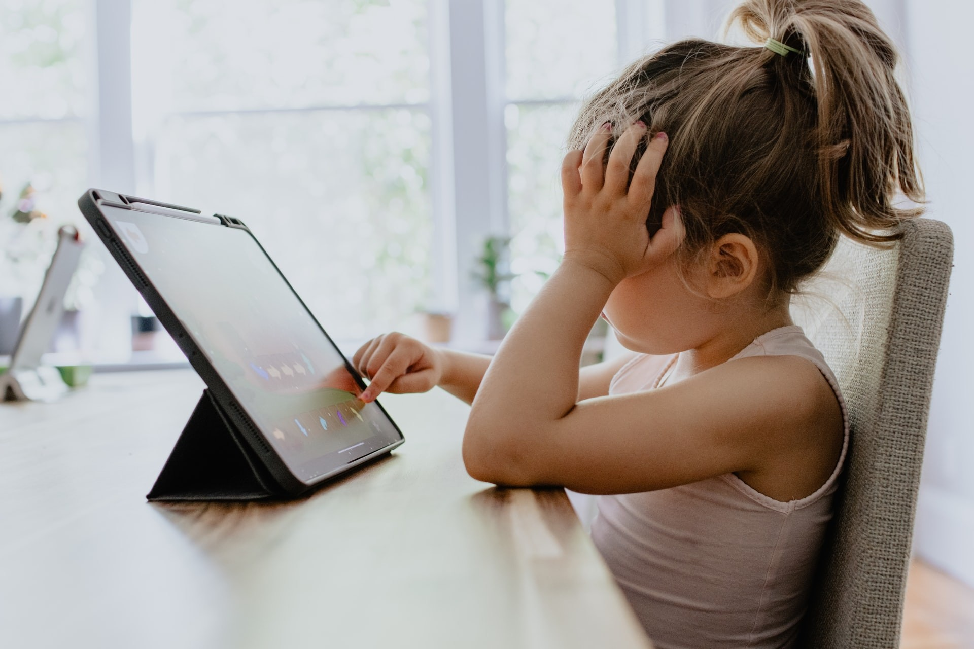 Young girl uses a tabled while completing a virtual learning assignment.