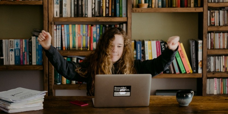 Student using laptop and raising arms in excitement.