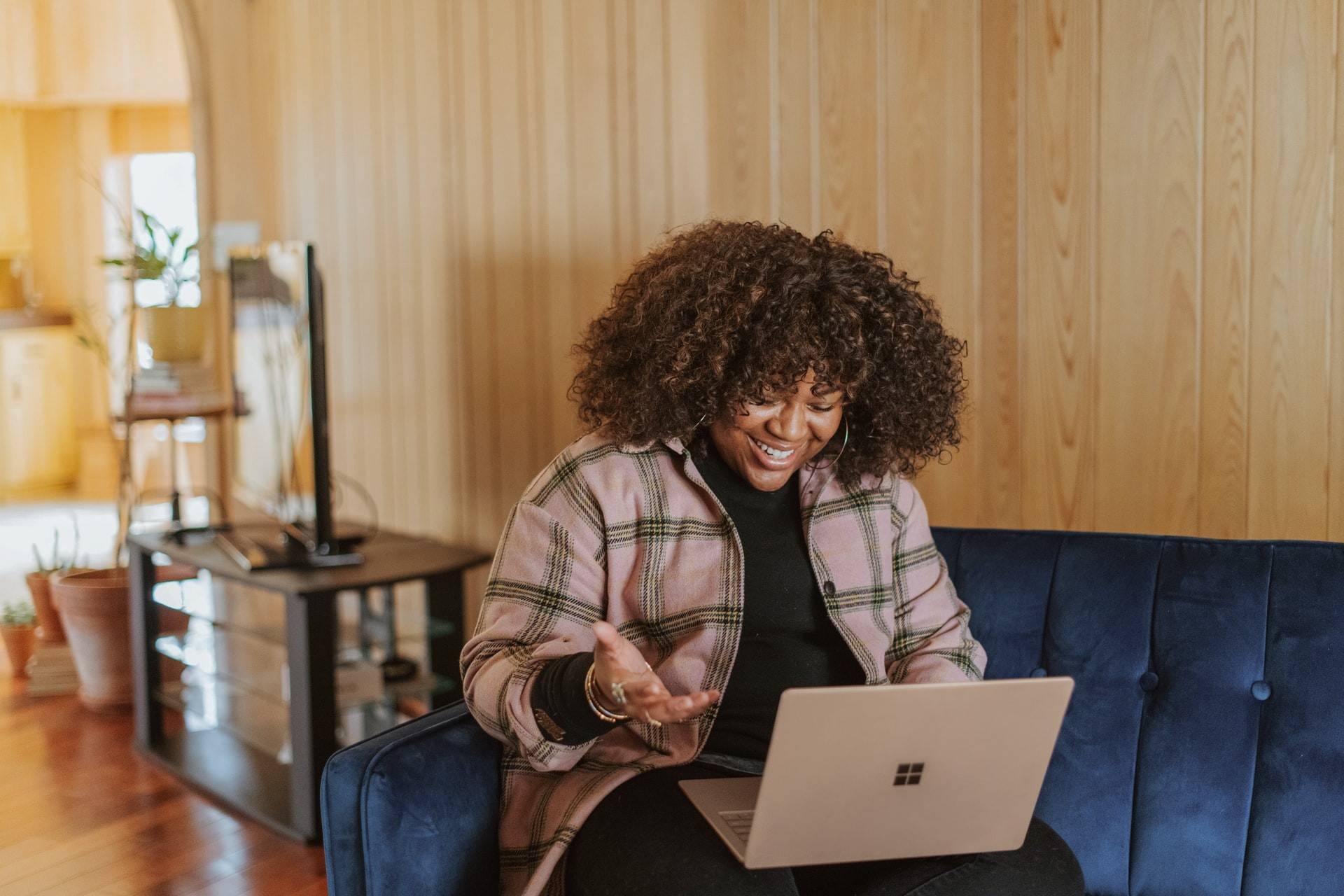 Woman sits on couch in her home and works on a laptop computer while she learns virtually.