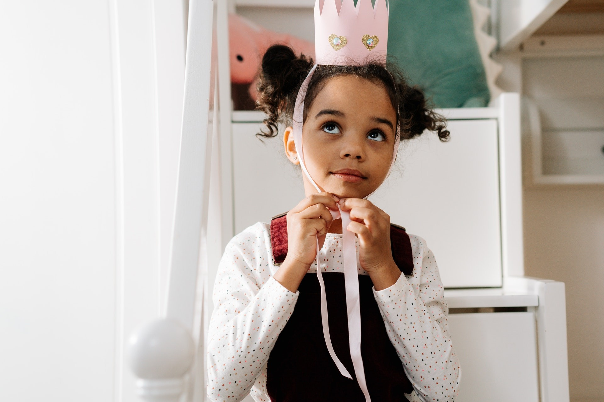 A young female kindergarten student plays dress up during play based learning activities.