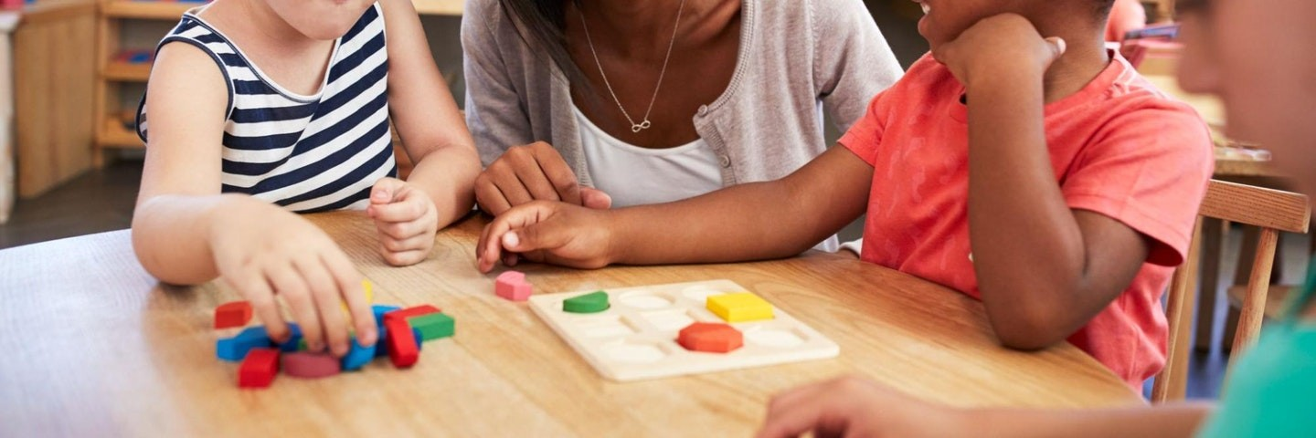 A teacher and two students use wooden blocks to do geometry activities.