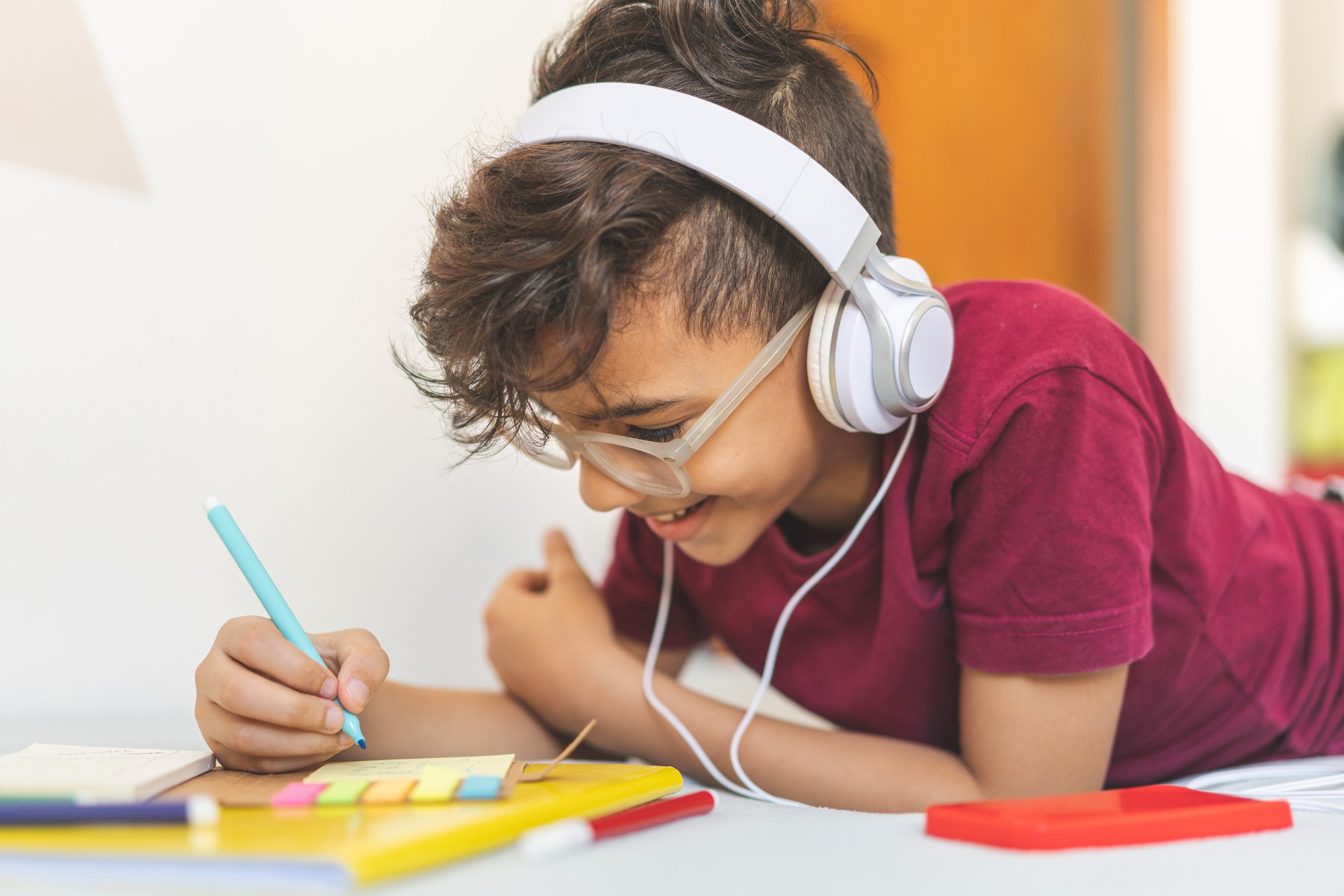 Child listening to headphones and smiling while writing notes.