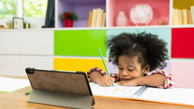 Girl writing in front of tablet.