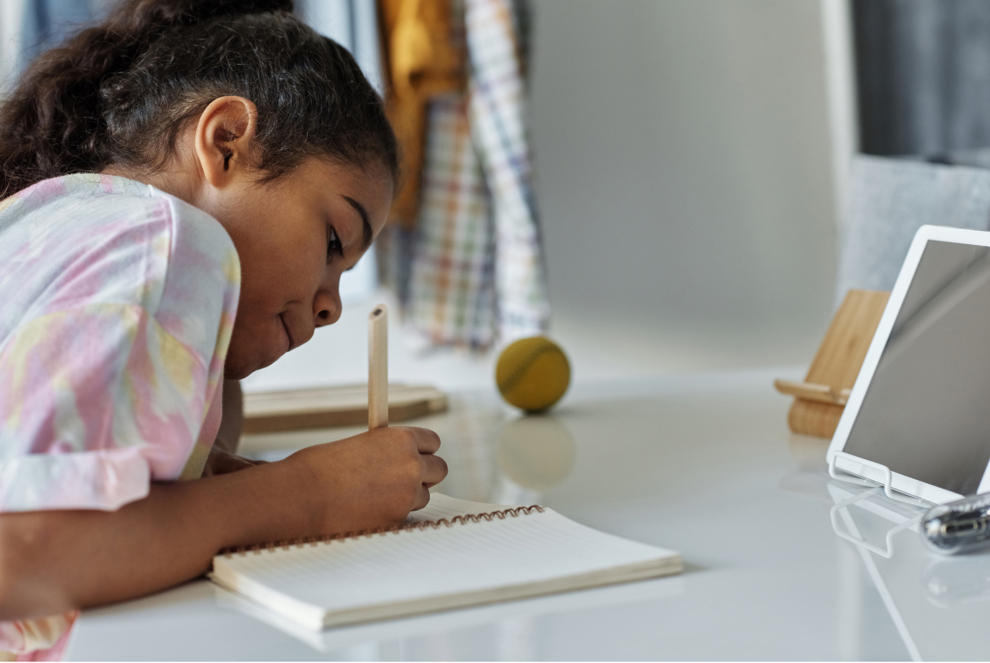 Child studying at a desk with a tablet device in front of her.