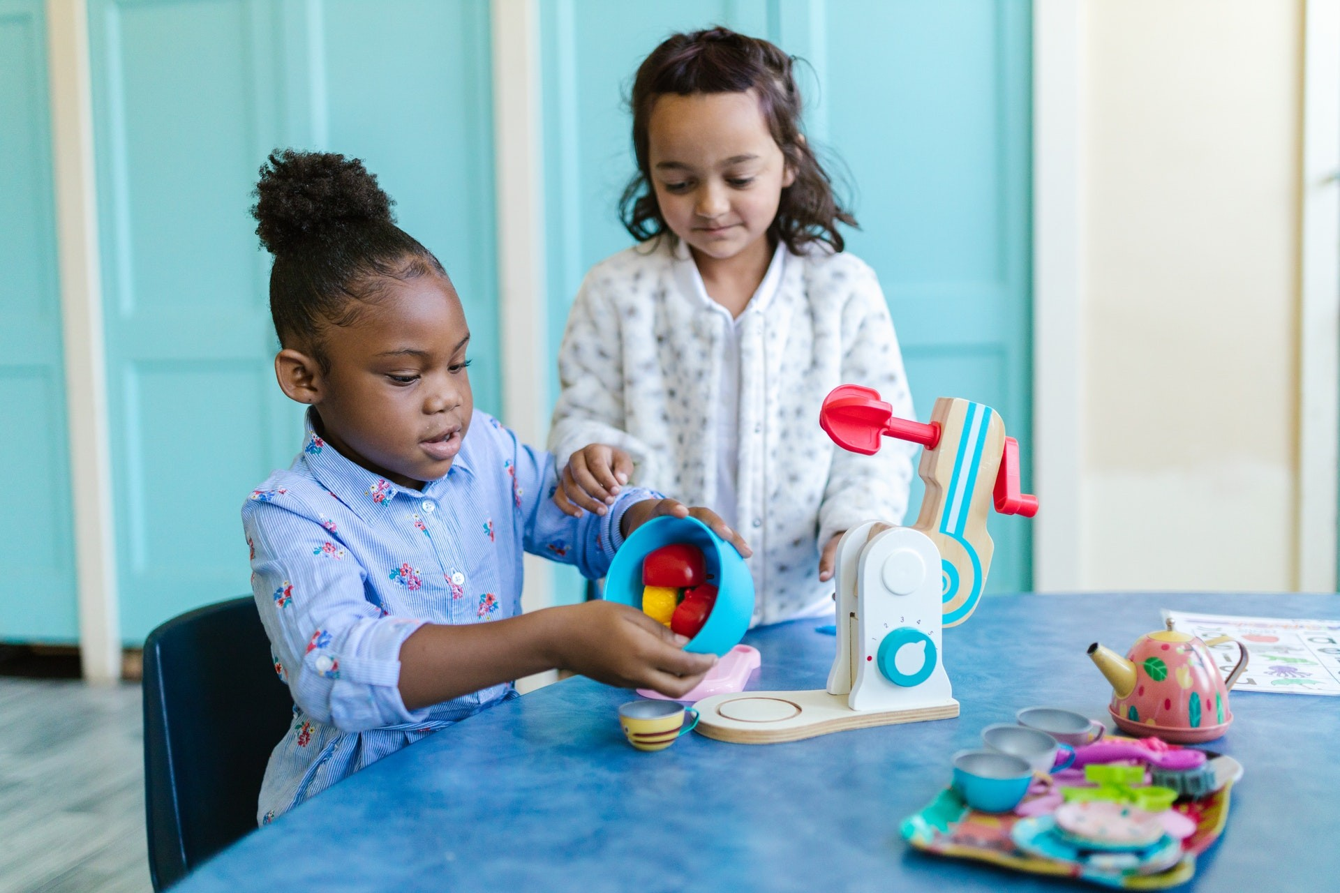 Two girls play with toys during play-based learning activities.