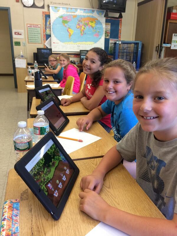Five students are smiling and playing Prodigy game