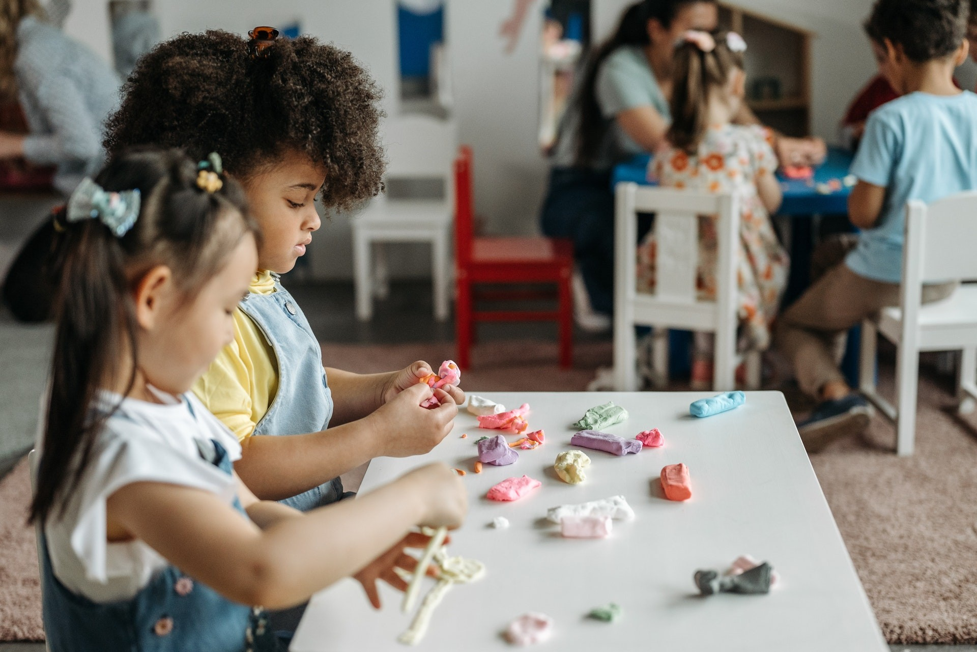 Two young girls play with playdough in a play-based learning classroom.