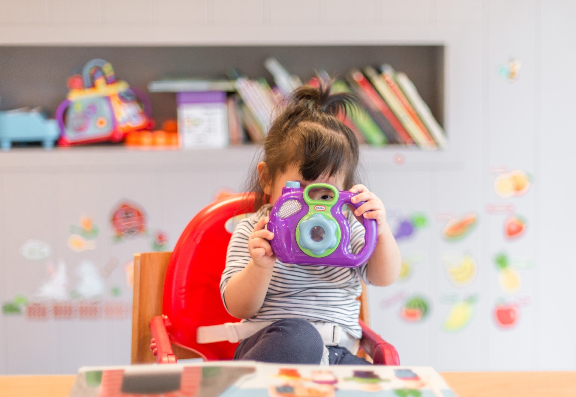 A young child plays with a toy camera in a classroom using play-based learning activities.