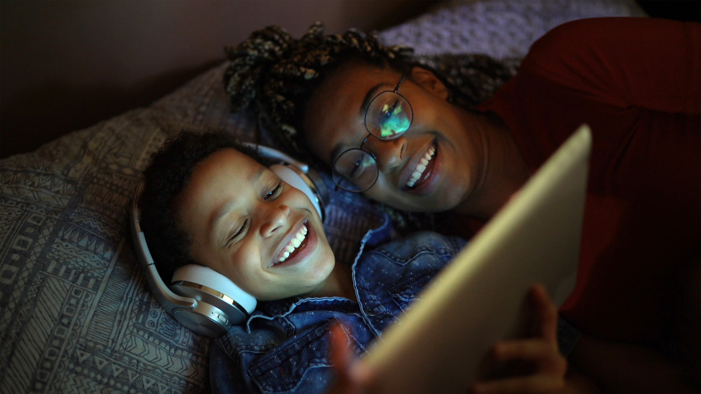 Parent and child smiling together while using a tablet device.