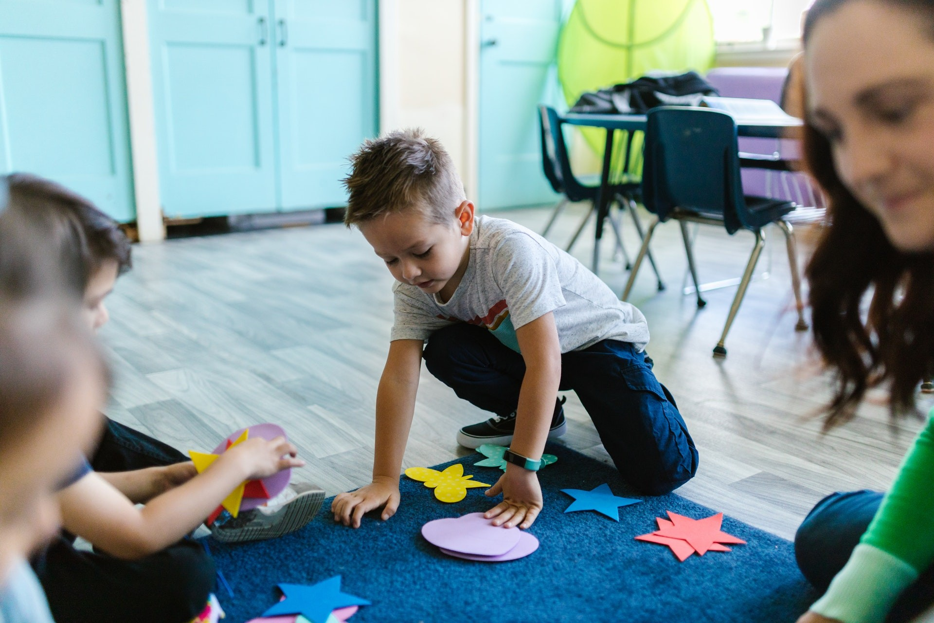 Students play with shapes on a mat in the classroom during a geometry activity