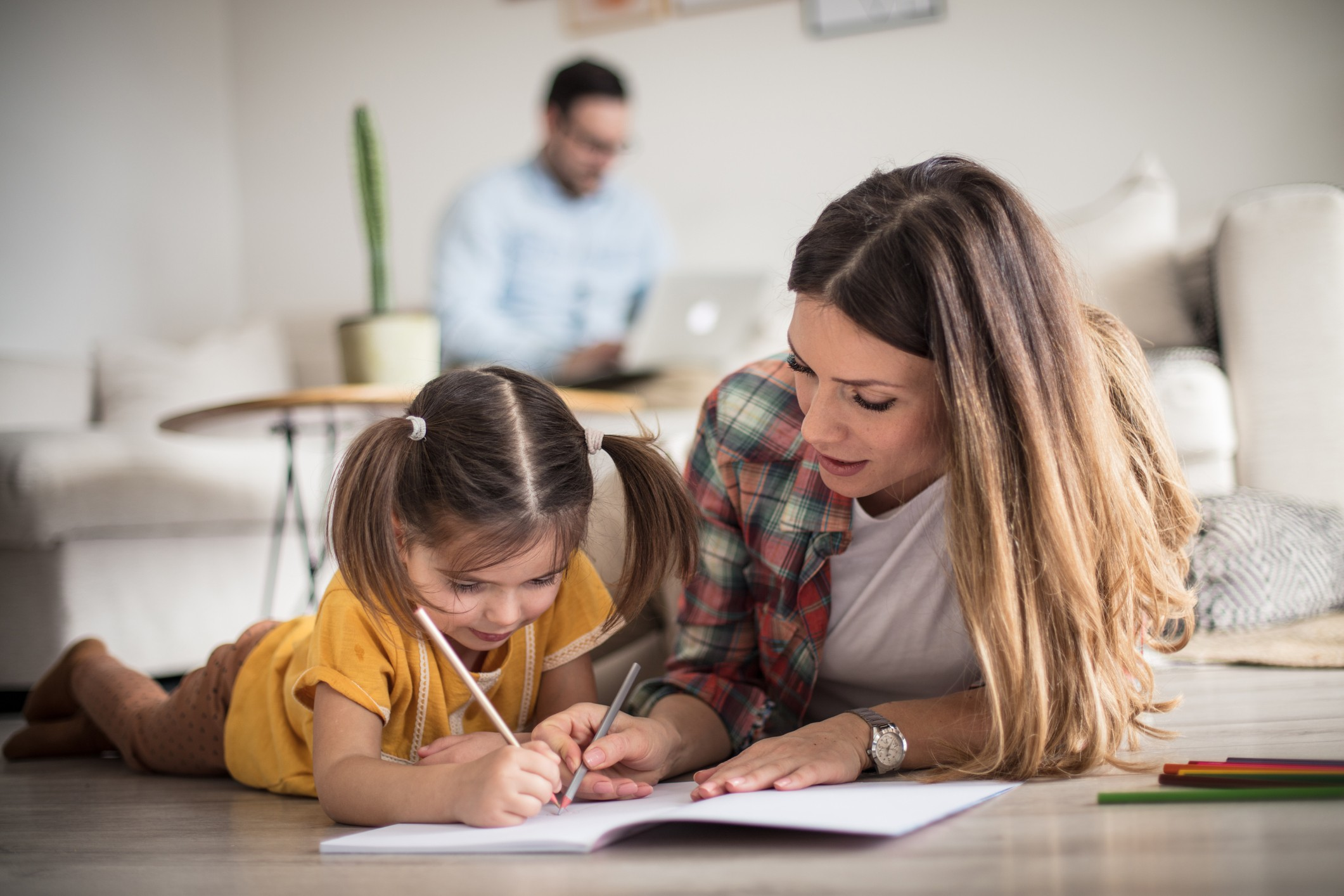 Mom helping her young daughter write notes in a notebook.