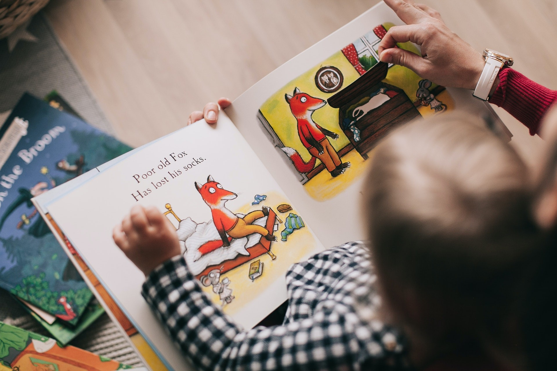 Overhead picture of a young child reading a book in a play-based learning classroom.