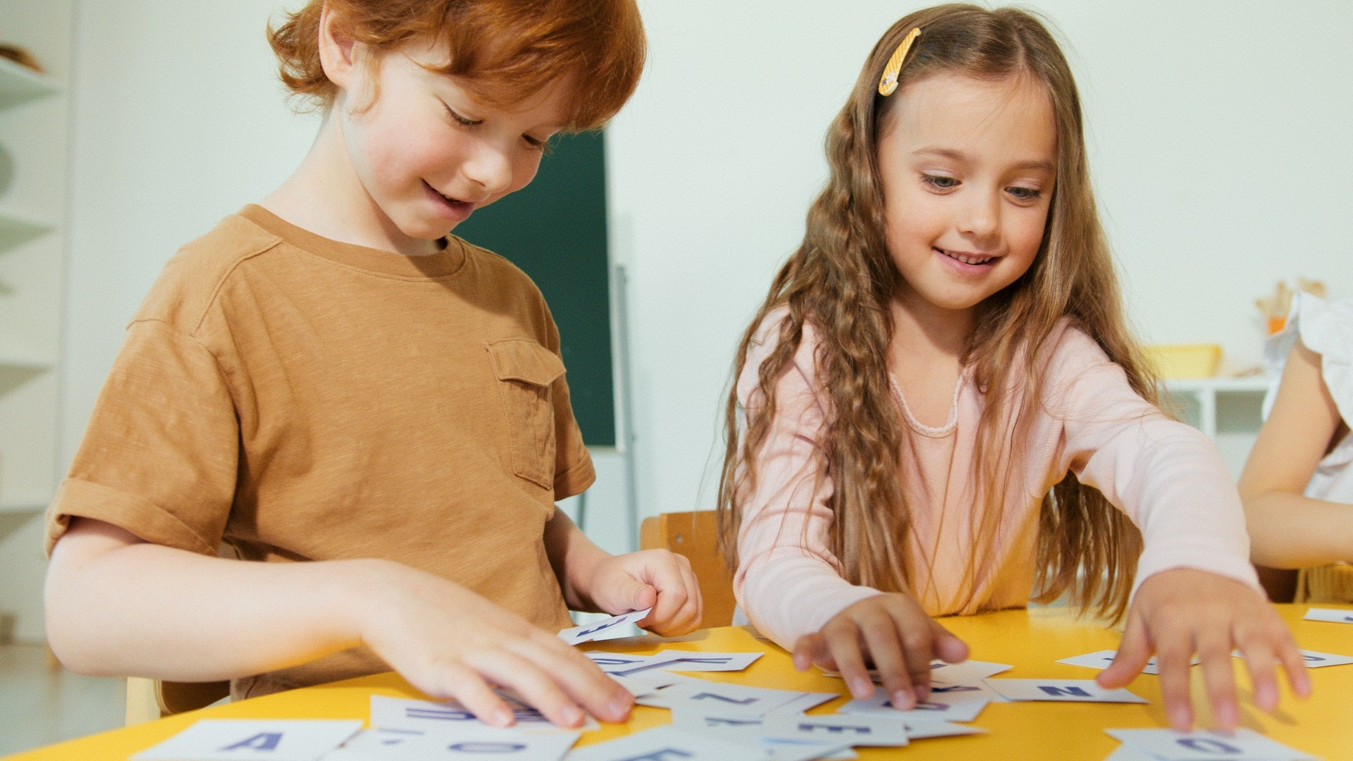 Two students work on a play-based learning activity in their classroom.