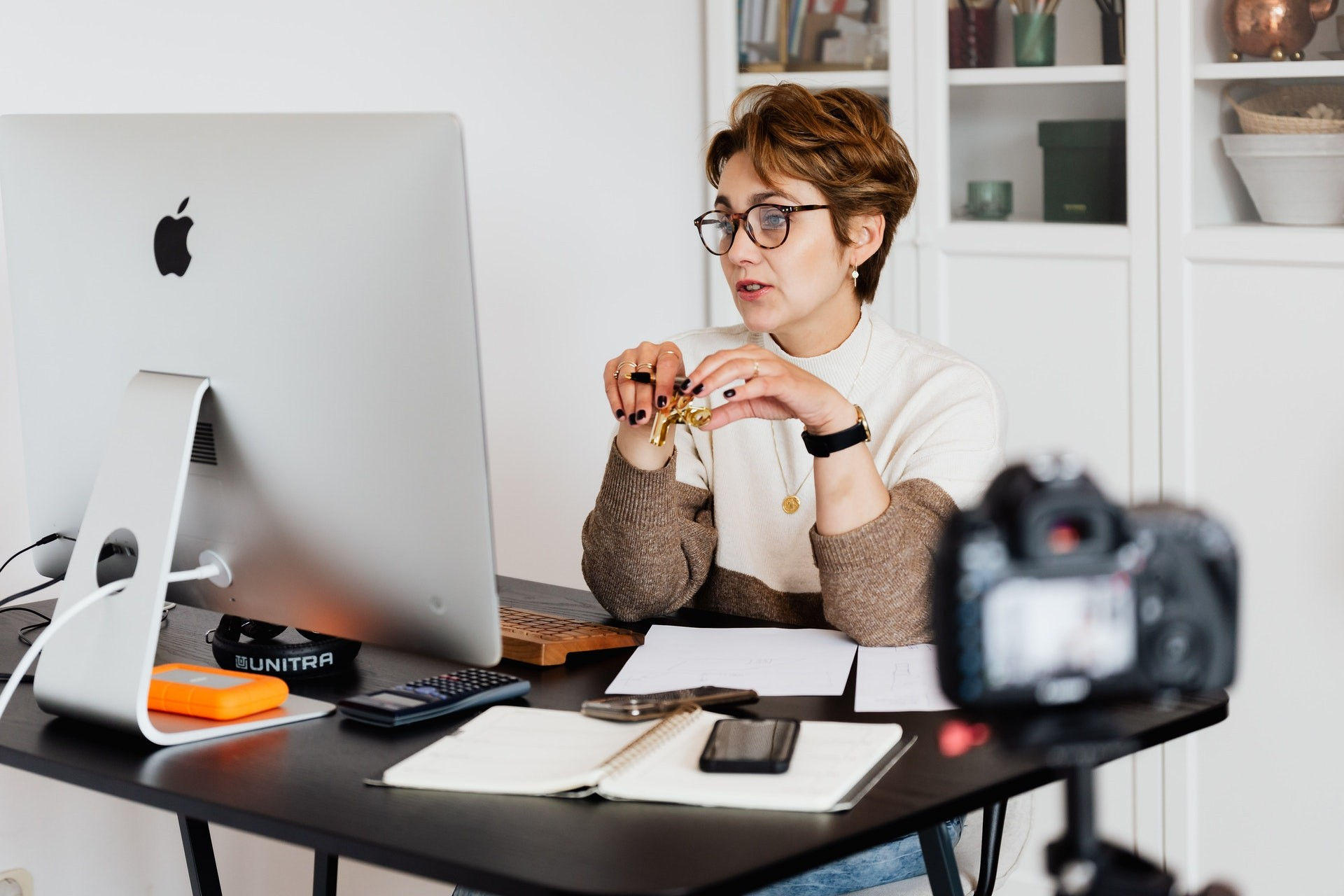 Female teacher sits at workstation with a camera set up to teach online.