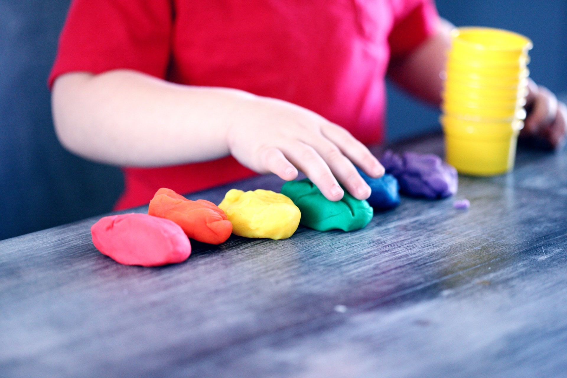 A young learner plays with playdough during geometry activities