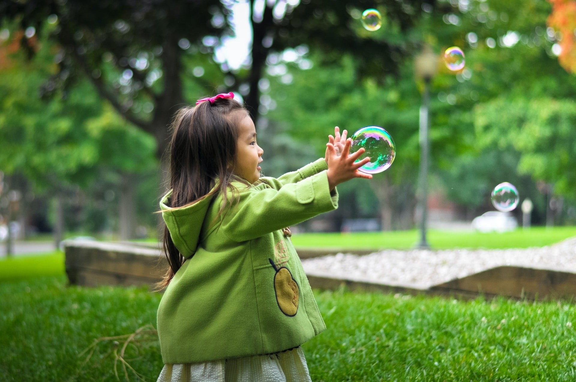 A young girl plays outside with bubbles to promote physical development through play-based learning activities.