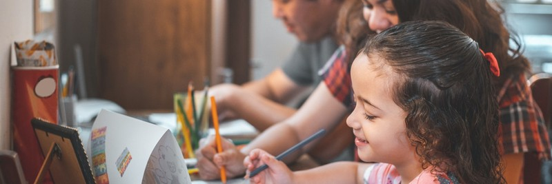 A father, mother and daughter sit at a table coloring something for spring break activities for kids.