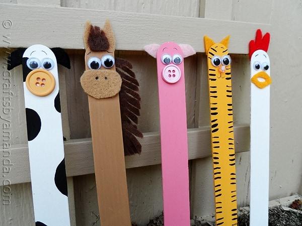 Row of popsicle sticks decorated as farm animals: a cow, horse, pig, cat and rooster.