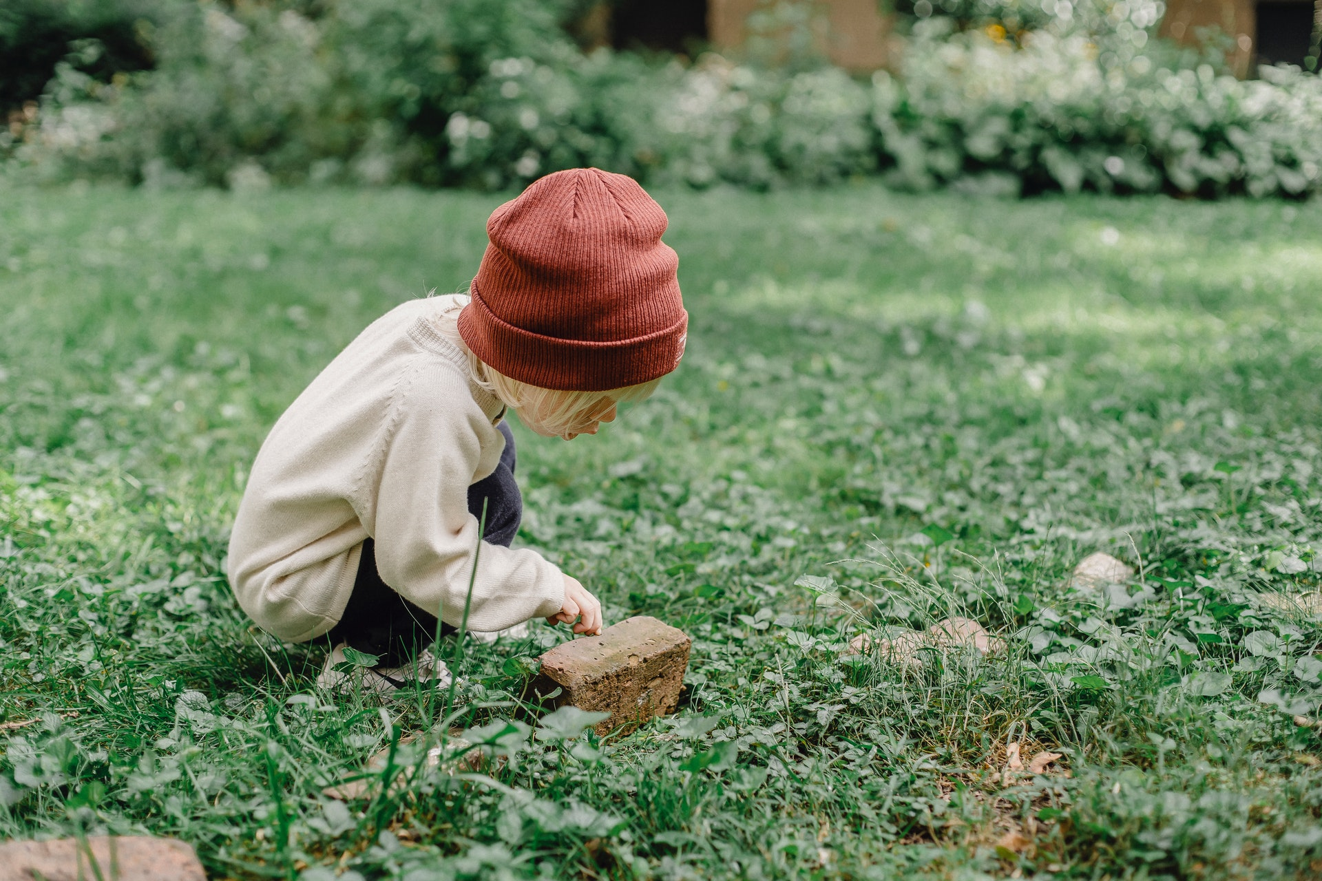 A young boy investigates a rock during some earth day activities for kids.