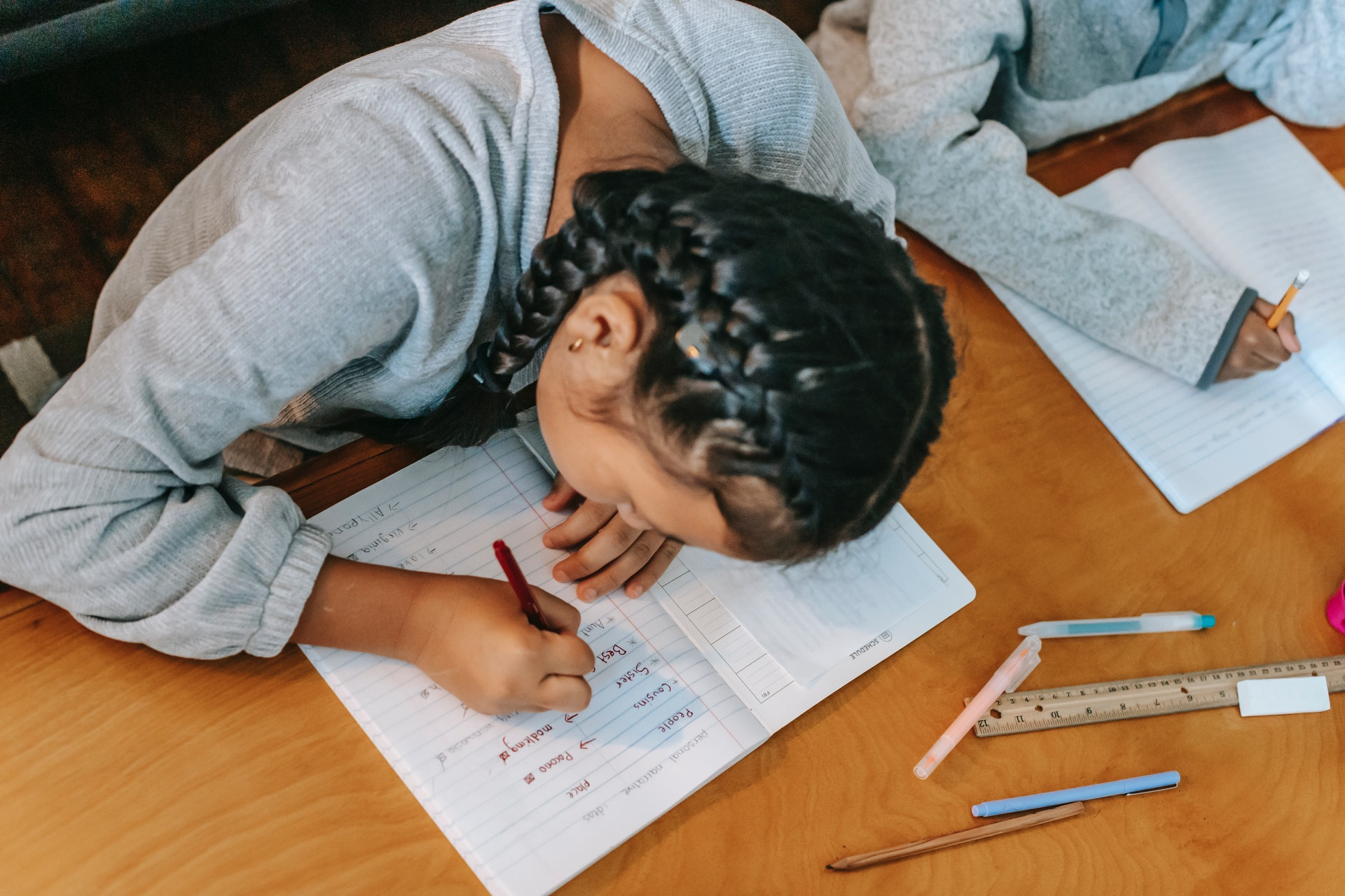 Top-down photograph of a girl with braids sitting at a desk next to another student and writing in a notebook.