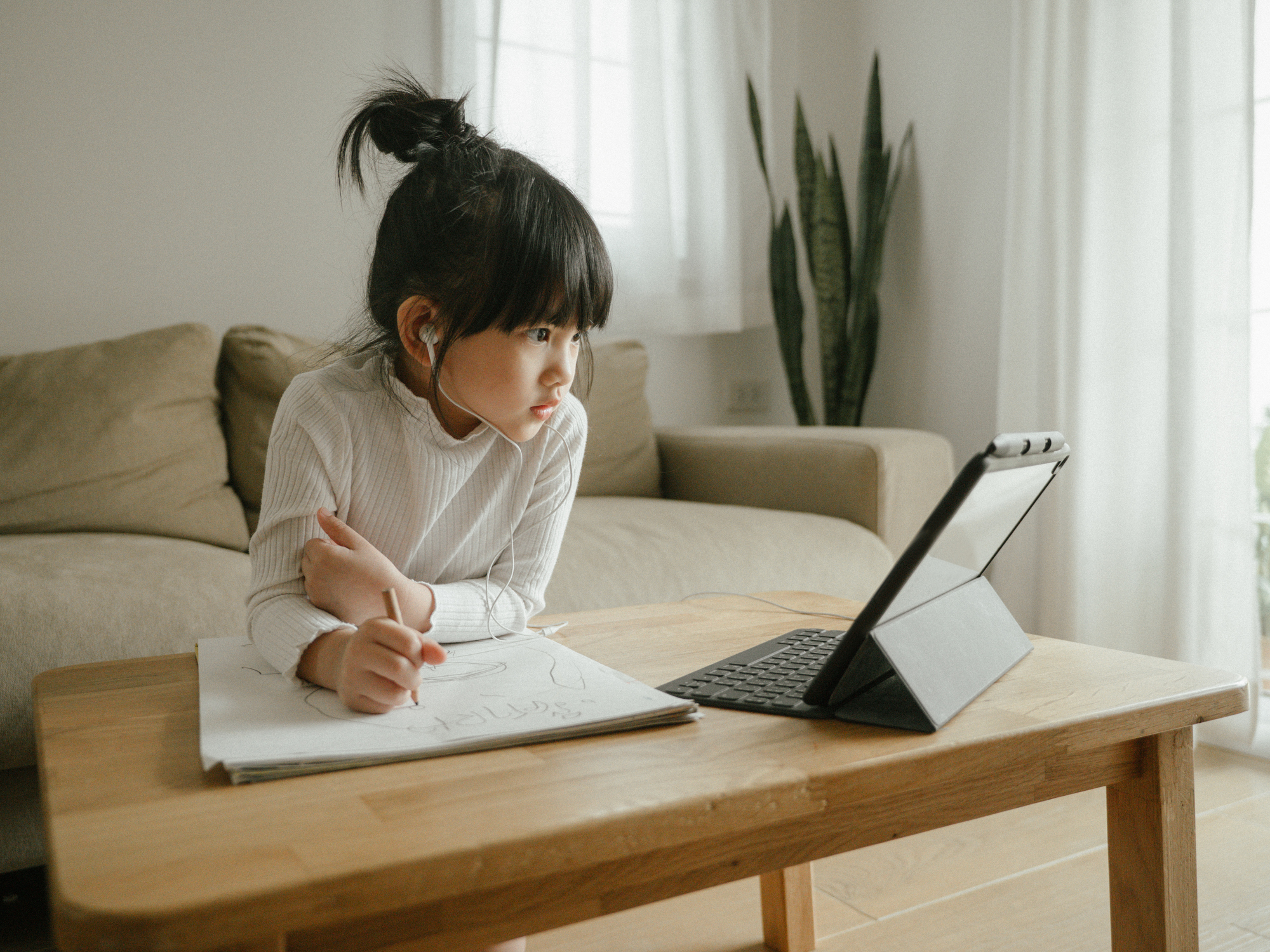 Young girl sitting at a table, watching something on her tablet while writing on a piece of paper with headphones in.