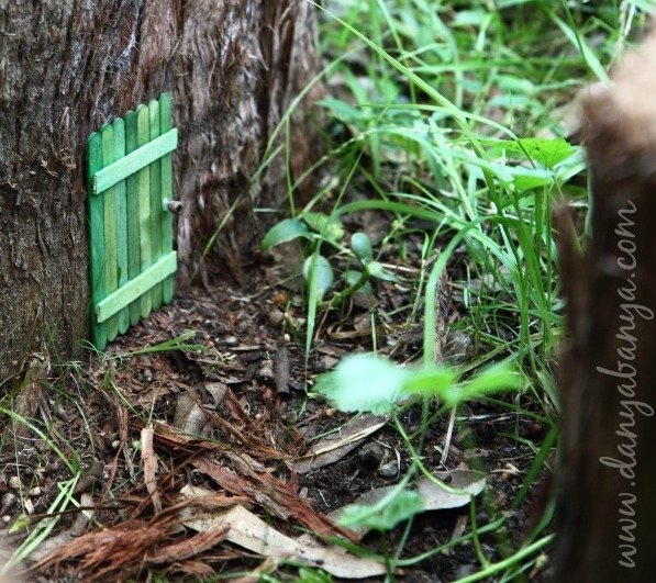 Small green fairy door placed at the bottom of a tree trunk in a garden.