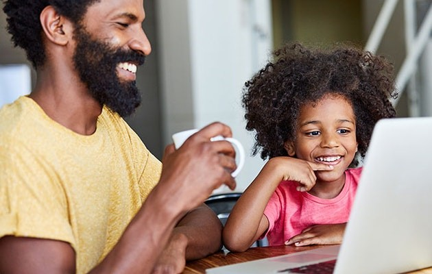 Daughter and father smiling in front of laptop.