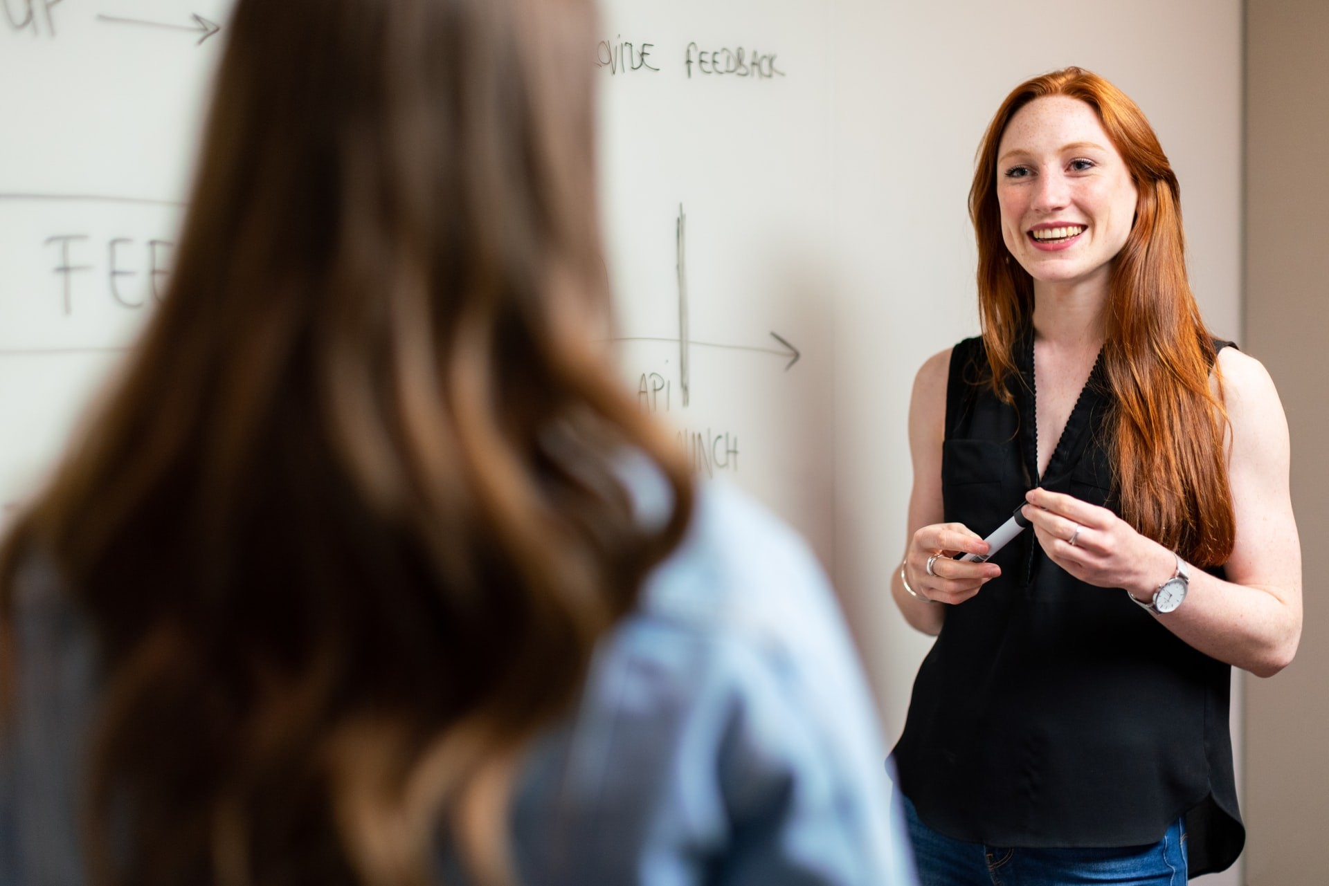 Female teacher with red hair stands in front of a blackboard talking to a student who has their back to the camera.