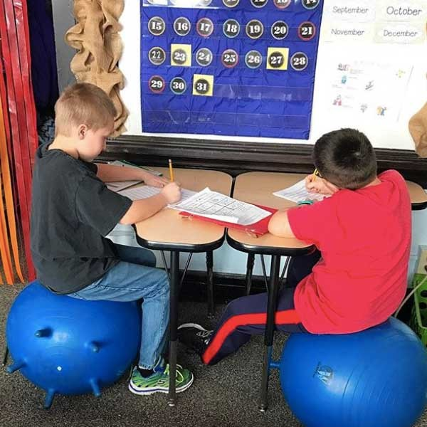 Two students doing school work on a small group table.