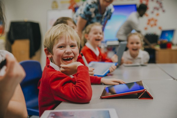 Young students sit smiling at a desk, using tablets to complete work.