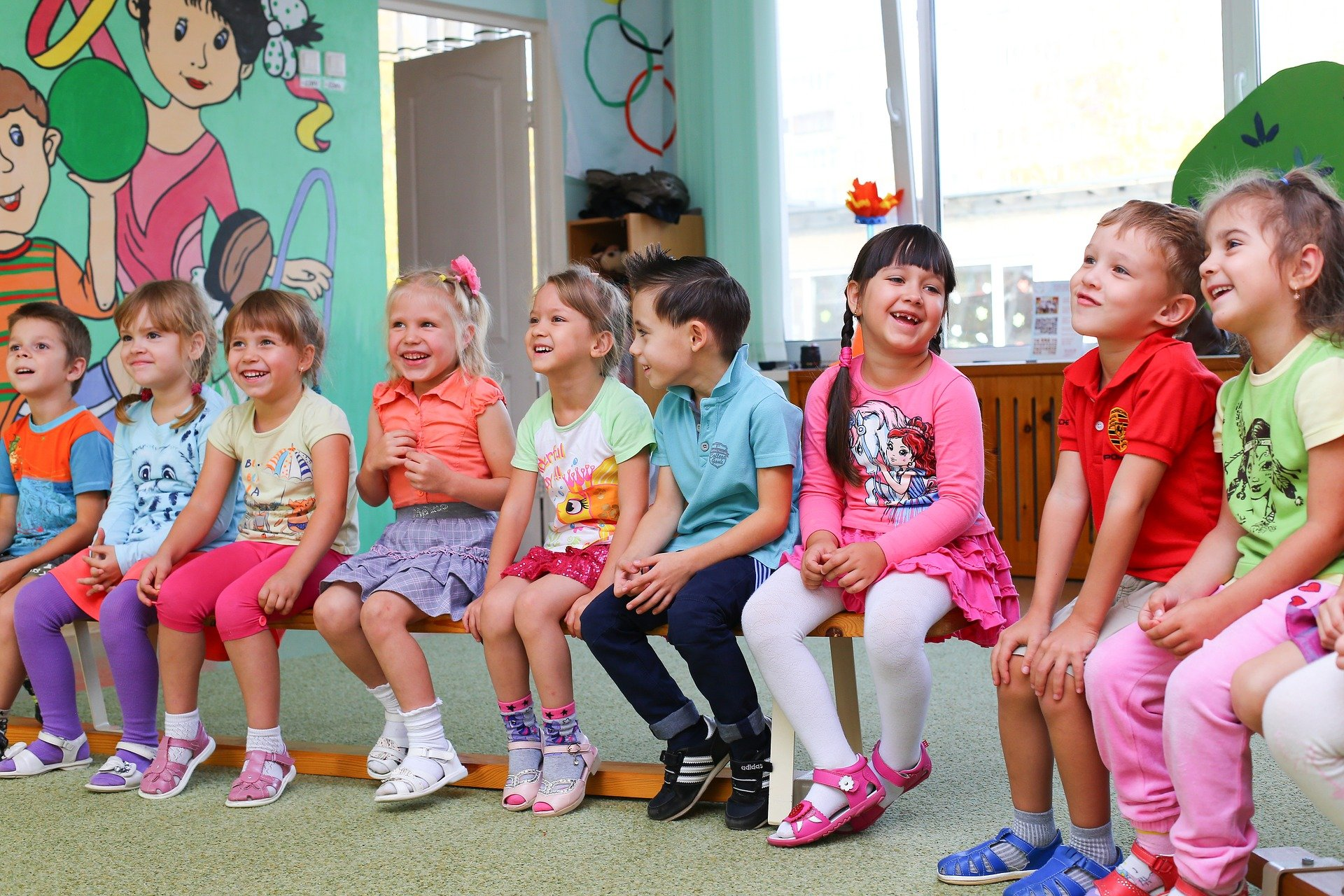 Nine kindergarten students sit in a row on wooden benches in a classroom.