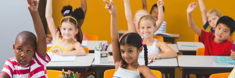 A class of young students sits at their desks and raises their hands