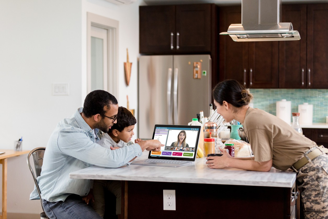 A preschool age boy and his parents watch the boy's preschool teacher during a live stream preschool class. The boy is distance learning during the COVID-19 pandemic.
