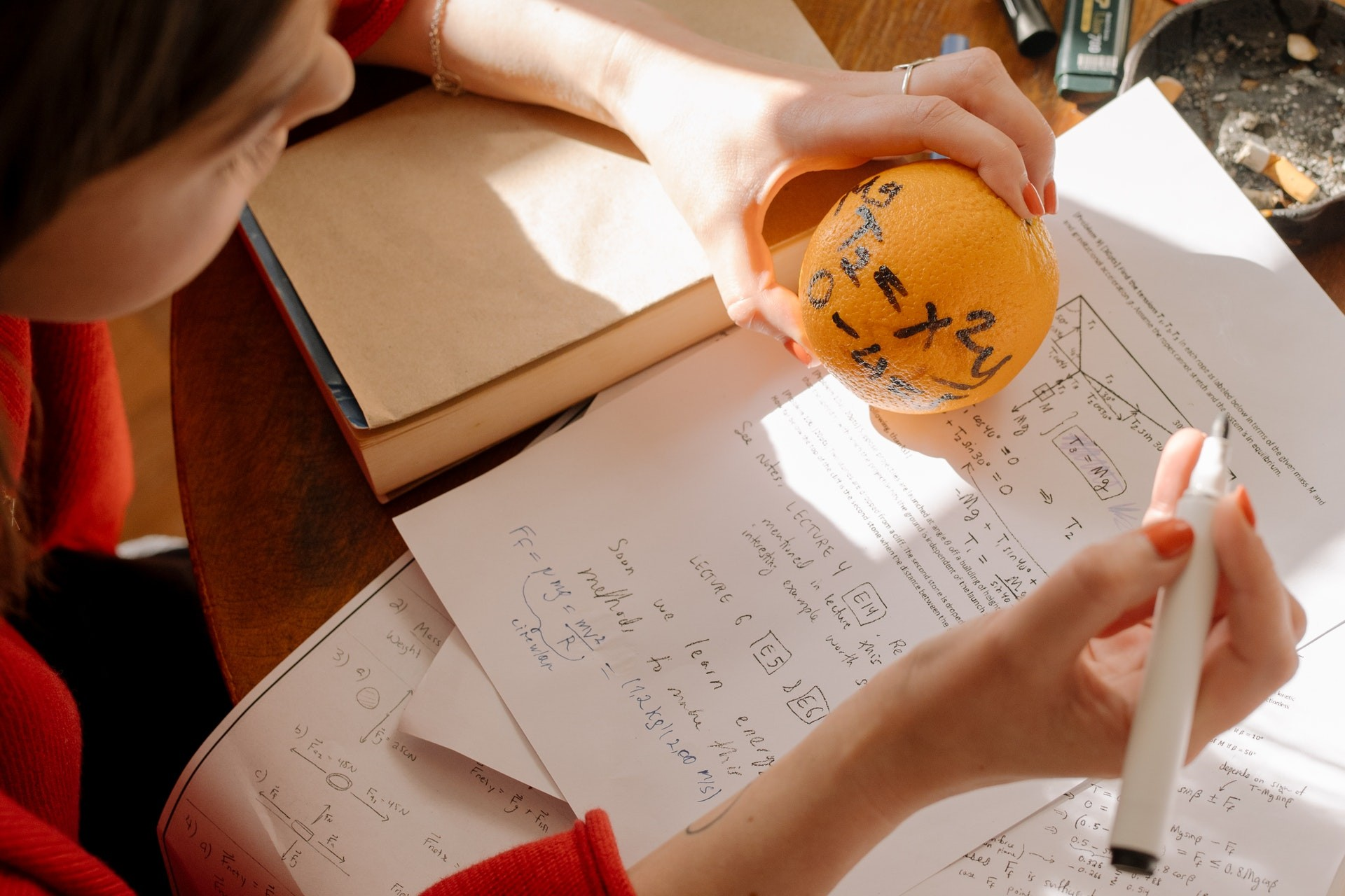 A student holds an orange with an equation written on it while working on a math writing prompt.