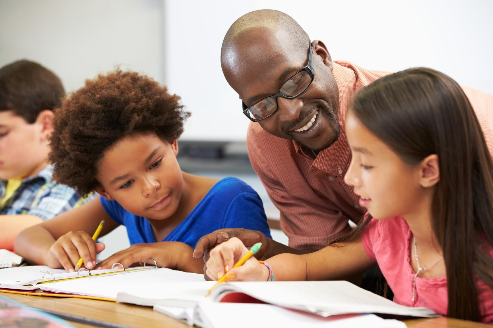 A teacher smiles at two young female students as they write in binders.