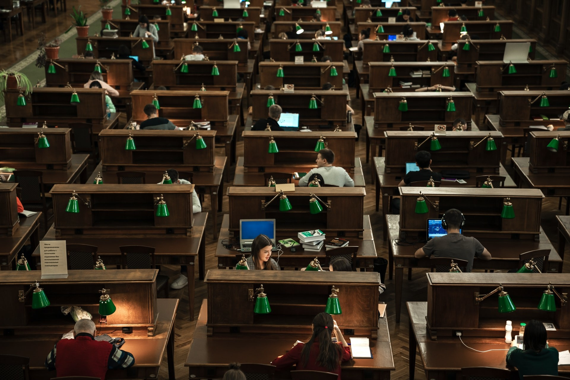 Overhead shot of students studying in a large college library.