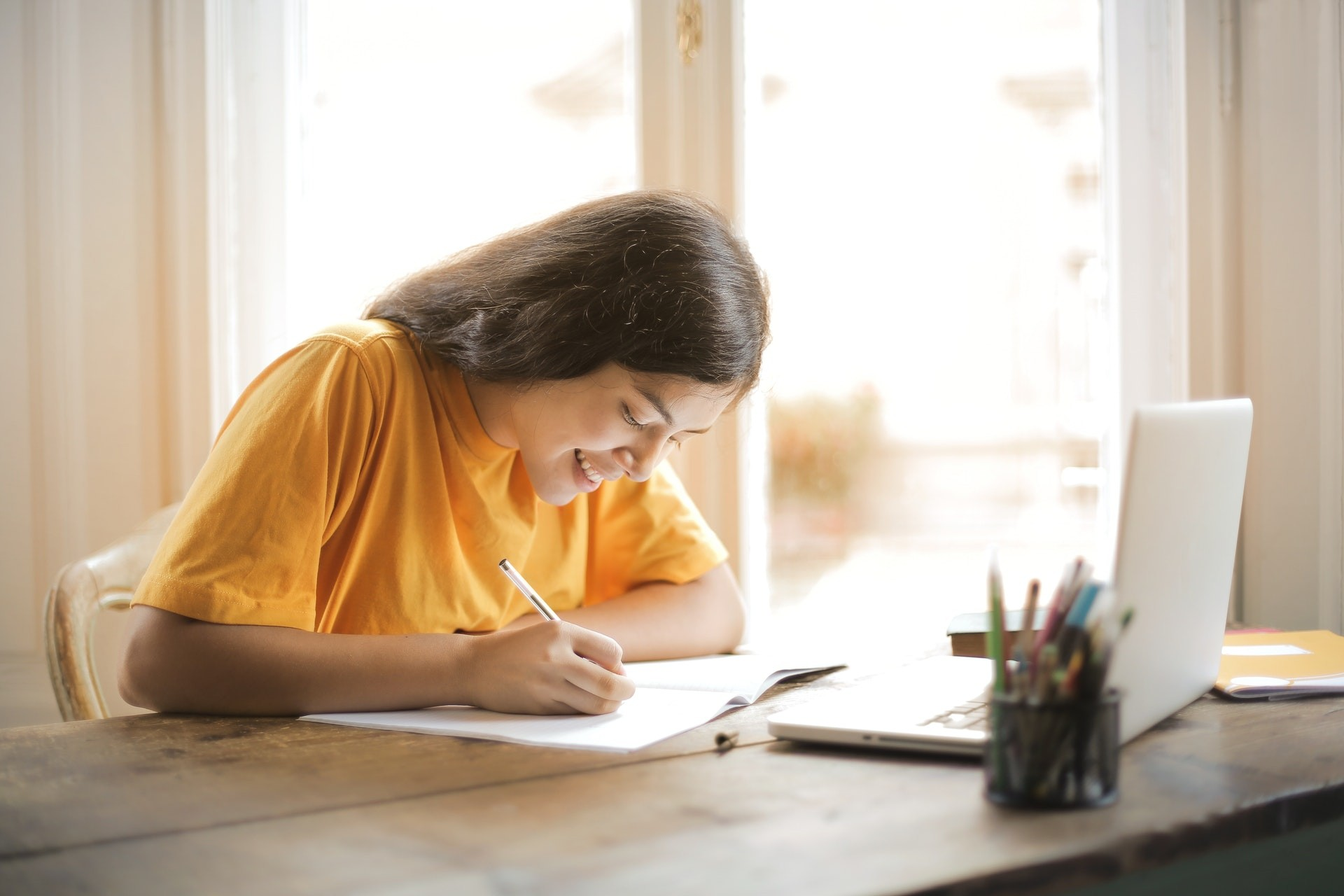 A student in a yellow shirt sits at a table and studies.