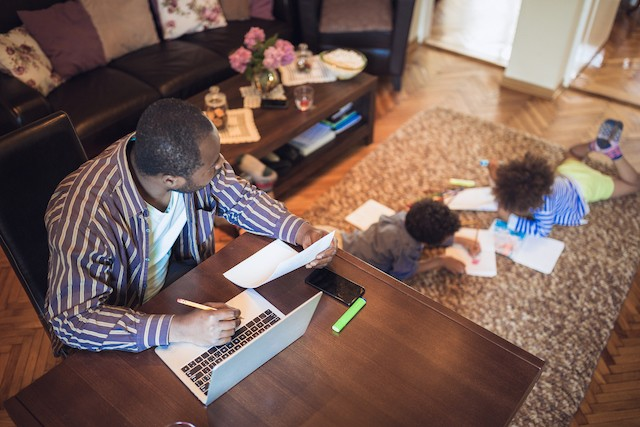 Father of two looks over at his kid doing homework on the carpet