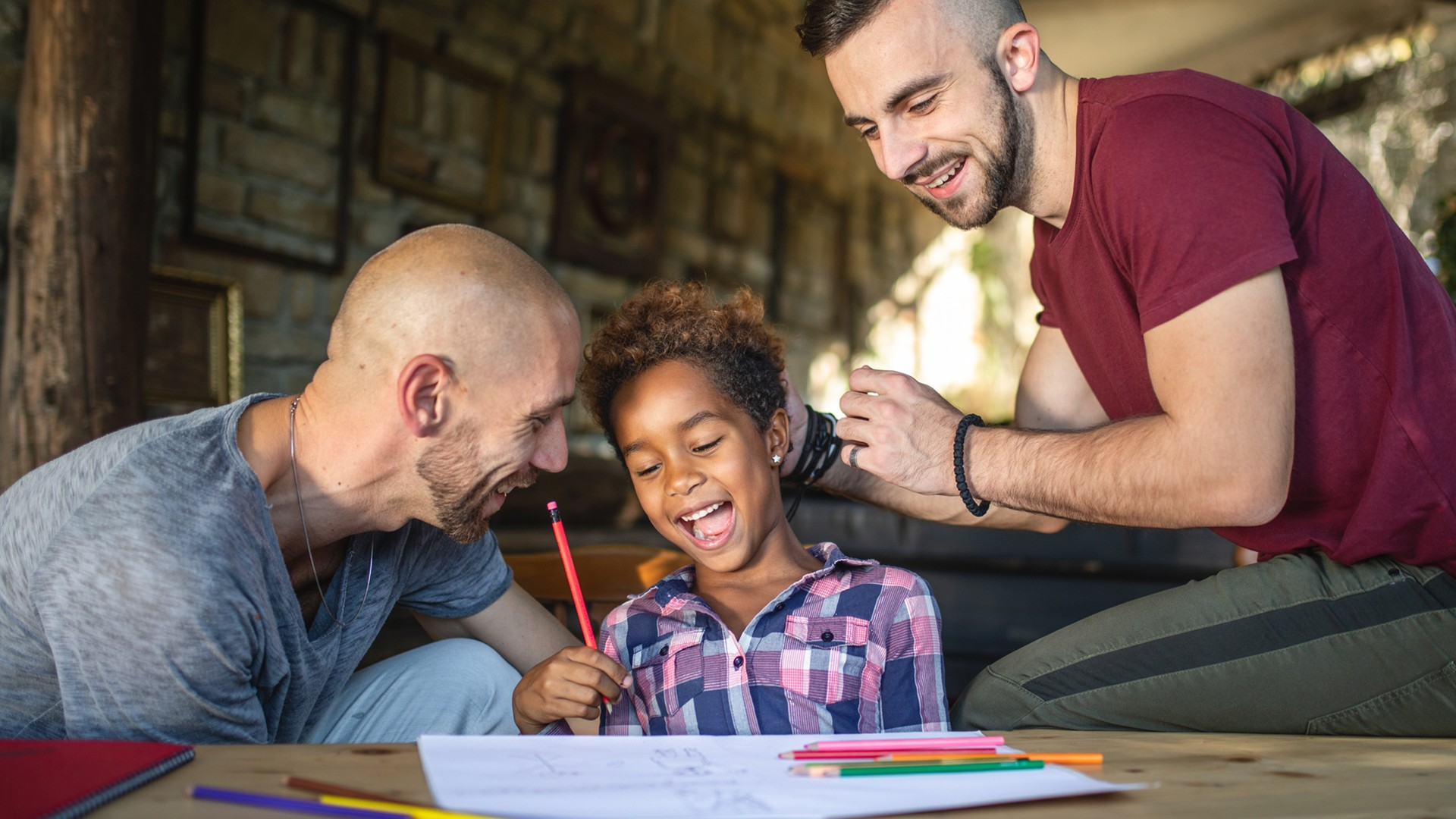 Two fathers and a young girl who is laughing work on completing a homework assignment at the table.