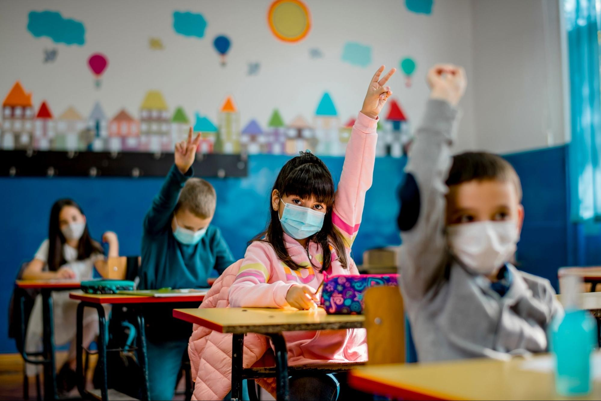 Four children sit in a row of desks, wearing masks and raising their hands, as they return to in-person learning after COVID-19.