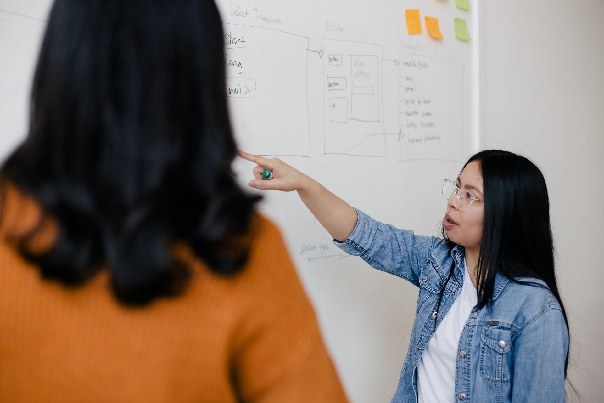 Two female students stand at a whiteboard and discuss a diagram.