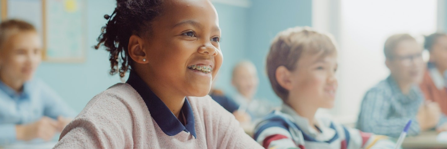 Young girl sits in a classroom smiling as she learns how to do long division.